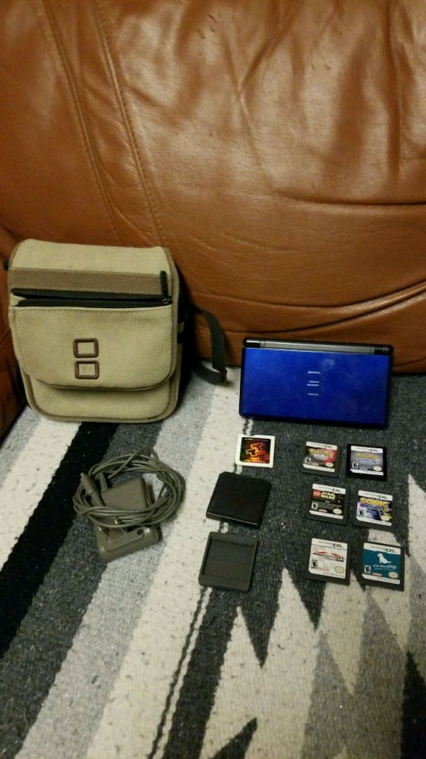 Blue and black Nintendo DS with game cartridges