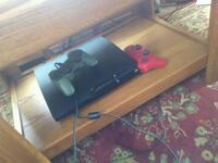 black Sony PS3 super slim console with controllers