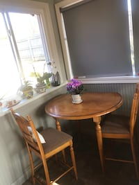 High wood round table with two chairs.