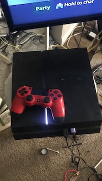 black Sony PS4 console with red controller