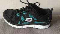 unpaired black and teal Skechers running shoe
