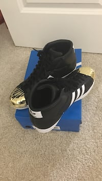 pair of black-and-gold Adidas Superstar high with box 51 km
