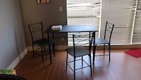 black metal dinning table 4 chairs plus summertime tablecloth  Surrey, V3Z