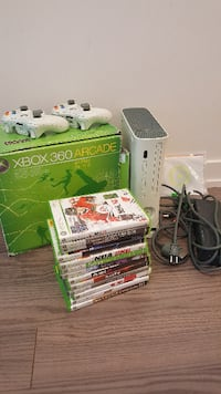white Xbox 360 Premium console with black AC adapter game cases, two white controllers, and game bundle box MISSISSAUGA