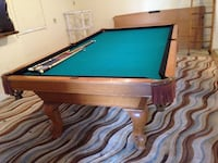 billiard pool table with several cue sticks