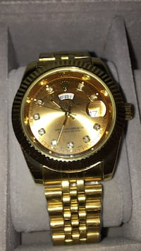 round gold Rolex day-date watch with link bracelet