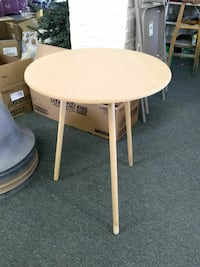 round white wooden pedestal table with glass top