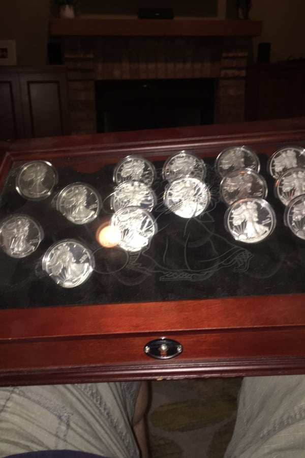 Cherry wood silver dollar case with a variety of silver dollars. $600 67b6334b-9f55-40c9-88a8-ab5d21e7deb6