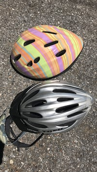 Two grey and pink-green-and-yellow stripe bicycle helmets