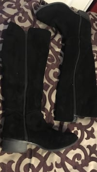 pair of black zipped knee high boots