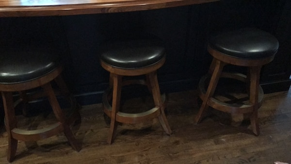 Three brown wooden bar stools