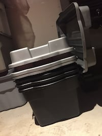 4 large plastic bins with swing lids.