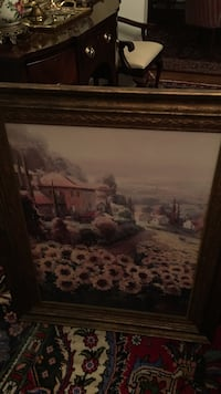 painting of sunflowers near pink building