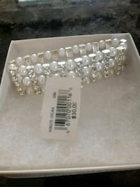 silver-colored bracelet with white beads and box