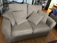 Beige loveseat with matching cushions