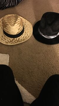 Two beige and black fedora hats