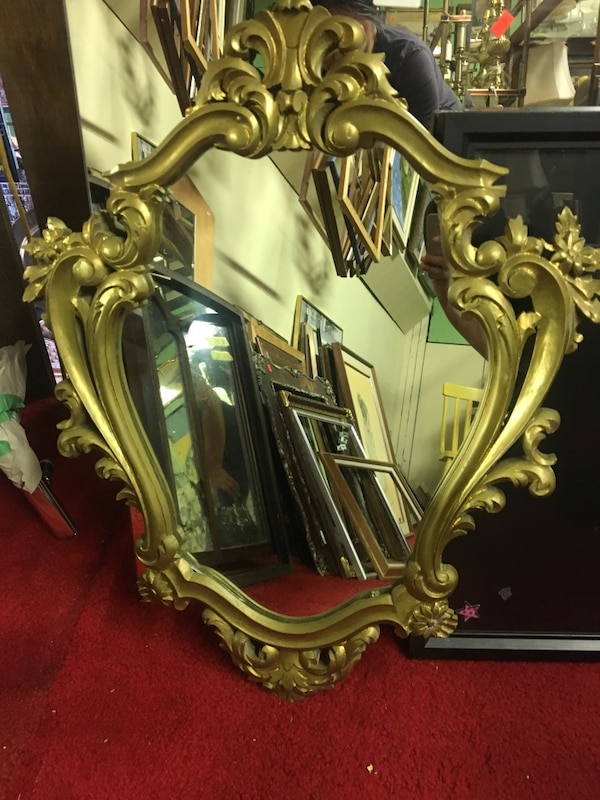 brass-colored framed mirror