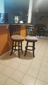 two brown wooden framed black leather padded bar stools