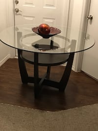 round glass top table with black wooden base