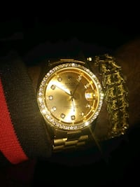 18K gold Rolex analog watch with gold link brace