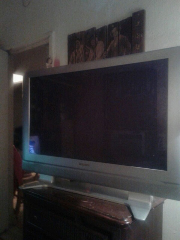 gray flat screen TV with brown wooden TV stand