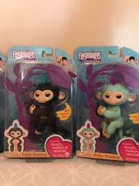 two black and green Fingerlings Baby Monkey toys