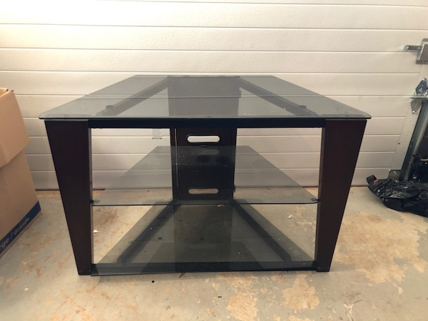Black wooden frame glass top tv stand in great condition .