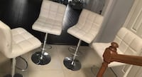 two stainless steel base white leather padded bar stools