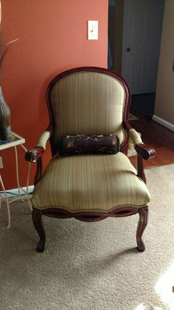 beige padded brown wooden armchair