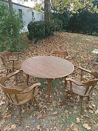 round brown wooden table with four chairs