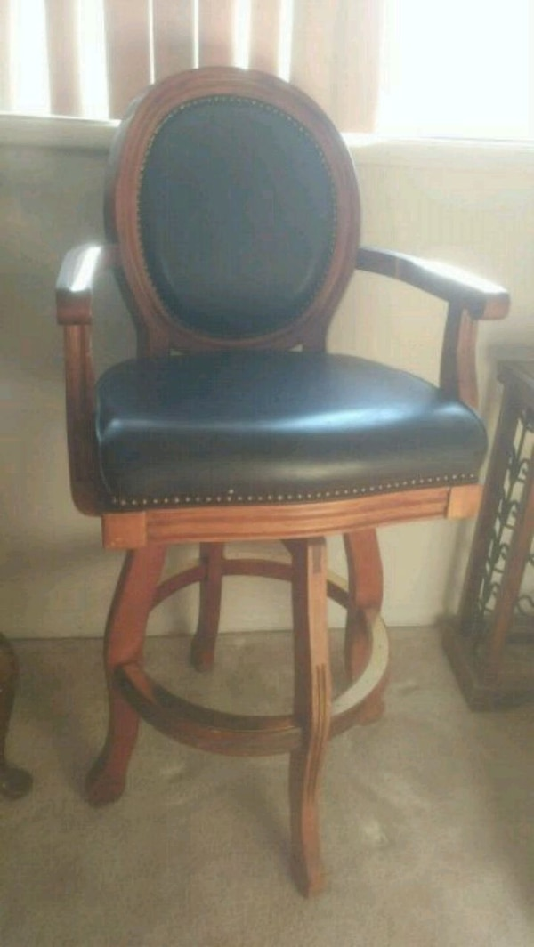 brown wooden framed black leather padded chair
