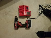 red Milwaukee cordless drill with charger