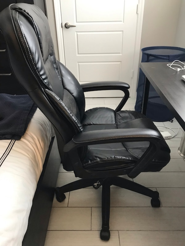 Black cushioned desk chair, adjustable height 3dafef87-99c6-40a3-8c2a-7f6e92a4946b