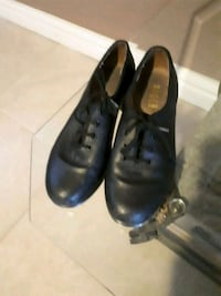 pair of black leather tap shoes
