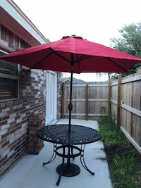 Round black metal patio table with red umbrella  Edinburg