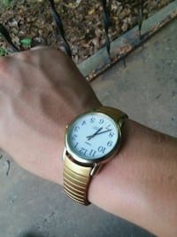 round white analog watch with gold link bracelet