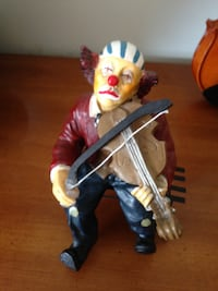 Clown Sitting on a Bench Playing a Violin