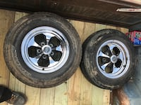 two black 5-spoke car wheels with tires