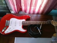 red and white stratocaster electric guitar