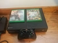 black Xbox one console with controller and games