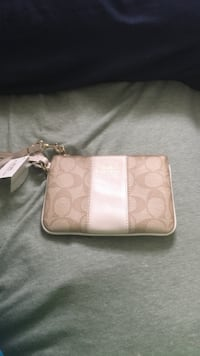brown and white Coach monogram leather wristlet