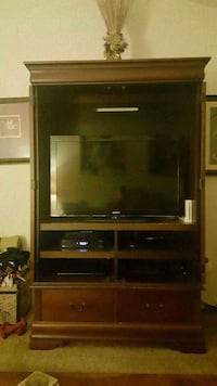 black flat screen TV with brown wooden TV hutch Costa Mesa, 92626
