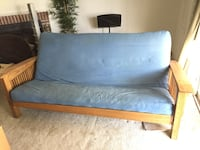 Blue padded sofa bed with brown wooden frame 50 km