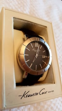round silver analog watch with black leather strap Vaughan