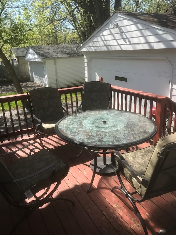 round black metal framed glass top patio table set
