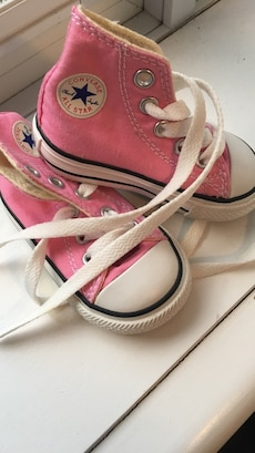 pair of pink Converse high top lace up sneakers