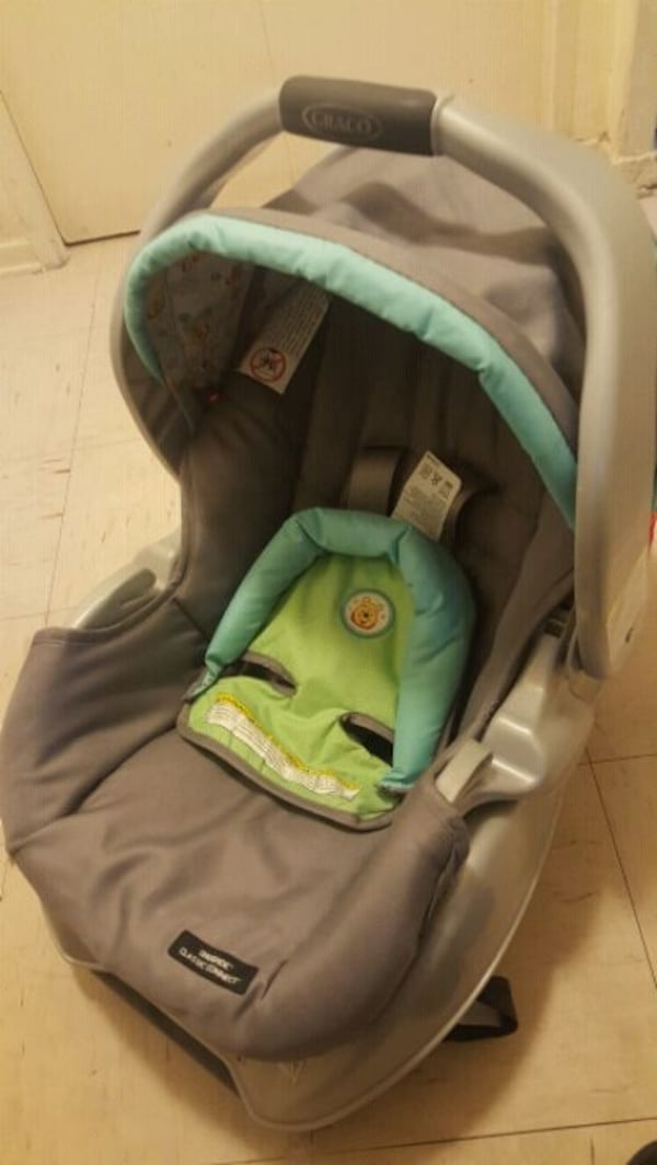 baby's gray and green car seat carrier. 6576950e-efc1-44d3-9348-6b52ffc69fc0