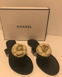pair of women's black-and-white Chanel leather flat sandals