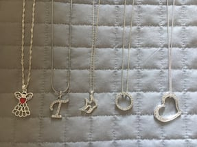 Five silver-colored chain link necklaces with pendants