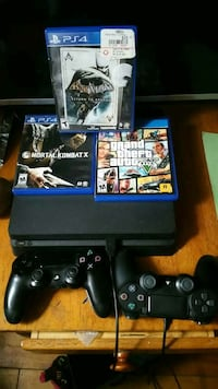 black Sony PS4 slim with controllers and game cases